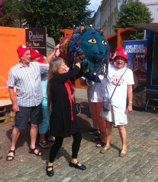"""PARAGRIFFEN KOMMER! Syngende besteforeldre med tekstilkunstner Elisabeth Medbøe i spissen. Sang/tekst ved Hege Rimestad: """"Når dragen stiger, stiger vi. Synker den, synker vi."""""""